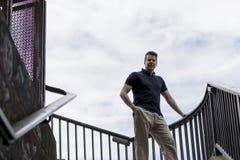 站立在一个室外楼梯间的人 免版税库存图片