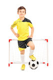 站立在一个小目标前面的小辈足球运动员 免版税库存照片