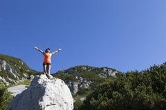 站立在一个岩石的俏丽的妇女远足者用被举的手 免版税库存图片