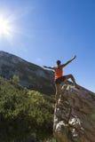 站立在一个岩石的俏丽的妇女远足者用被举的手 免版税库存照片
