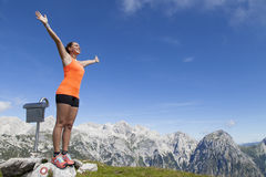 站立在一个岩石的俏丽的妇女远足者用被举的手 免版税图库摄影