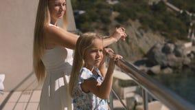 站立在一个开放阳台的母亲和女儿俯视海 图库摄影