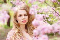 站立在一个开花的庭院里的年轻白肤金发的妇女 免版税图库摄影