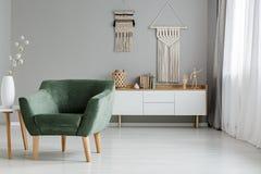 站立在一个明亮的客厅的一把绿色扶手椅子的真正的照片 库存图片