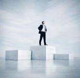 站立在一个最高的立方体的商人 3d 免版税库存图片