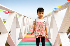 站立在一个木桥的亚裔矮小的中国女孩 免版税图库摄影