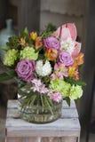 站立在一个木箱的花原始的花束在屋子里 免版税库存照片