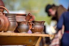 站立在一个桌和模糊的人上的泥罐穿中世纪服装在圣乔治的国际骑士节日比赛 图库摄影
