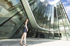 站立在一个现代商业中心的背景中的女商人 免版税图库摄影