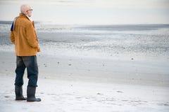 站立在一个空的海滩的成熟人 免版税库存图片
