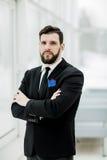站立在一个窗口附近的成功的商人在明亮的办公室 免版税库存图片