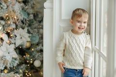 站立在一个窗口附近的迷人的小男孩小孩,在光 免版税库存图片