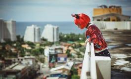 站立在一个红色衣服恶魔的屋顶和神色的万圣夜女孩下来从太阳照亮的城市的屋顶 库存图片