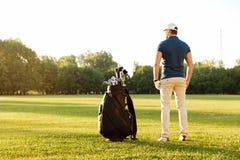 站立在一个绿色领域的后面观点的一个年轻人 免版税库存照片