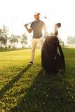 站立在一个绿色领域的年轻男性高尔夫球运动员 免版税图库摄影