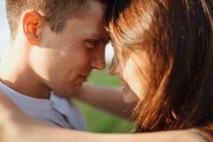 站立在一个绿色领域,反对天空,在胳膊和看彼此的年轻,愉快,爱恋的夫妇,做广告和  免版税图库摄影
