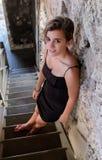 站立在一个老木楼梯的俏丽的西班牙十几岁的女孩 免版税库存图片