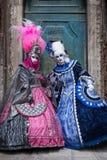 站立在一个老蓝色门前面的明亮地色的服装的两名妇女在威尼斯在狂欢节期间 免版税库存照片