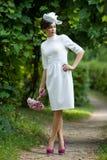 站立在一个葡萄园旁边的鞘礼服的新娘在一个夏天晚上 库存照片