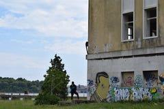站立在一个被放弃的大厦附近的男孩 库存照片