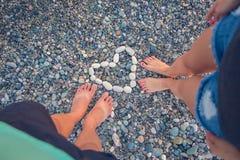 站立在一个被环绕的小卵石石头的少妇和男孩 享用一个异常的海滩,在的小卵石的女孩和男孩 免版税库存照片