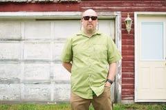 站立在一个被风化的车库前面的人 免版税库存图片