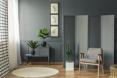 站立在一个装饰,灰色屏幕前面的椅子在a旁边 库存照片