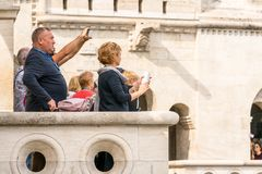 站立在一个观点的一个白种人男性和女性游人的侧视图和在马赛厄斯教会下外在布达佩斯 库存图片