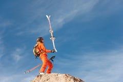 站立在一个高岩石边缘的滑雪者运动员在他的手上平衡他的滑雪避免蓝天和触毛 免版税库存照片