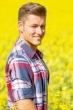 站立在一个黄色领域的英俊的白肤金发的人 免版税库存图片