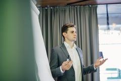 站立在一个活动挂图和当前项目前面的确信的年轻团队负责人或经理在办公室 库存图片