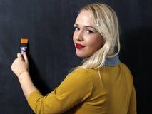 站立在一个黑暗的黑板前面的白种人妇女 绘画 免版税图库摄影