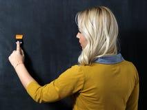 站立在一个黑暗的黑板前面的白种人妇女 绘画 库存照片