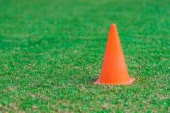 站立在一个绿草足球场的橙色锥体 库存照片