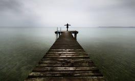 站立在一只木跳船的妇女 一个码头的招呼的妇女在湖有大开的胳膊的海 免版税库存图片