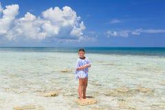 站立在一块小石头的Smilling快乐的愉快的小女孩在海洋在晴朗的华美的天 免版税库存图片