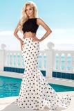 站立在一套长的婚礼礼服的一个专属水池旁边的美好的白肤金发的女性模型 免版税图库摄影