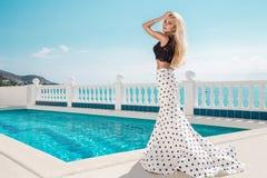 站立在一套长的婚礼礼服的一个专属水池旁边的美好的白肤金发的女性模型 免版税库存照片