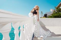 站立在一套长的婚礼礼服的一个专属水池旁边的美好的白肤金发的女性模型 图库摄影