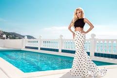 站立在一套长的婚礼礼服的一个专属水池旁边的美好的白肤金发的女性模型 库存照片