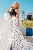站立在一套长的婚礼礼服的一个专属水池旁边的美好的白肤金发的女性模型 免版税库存图片