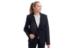 站立在一套黑衣服和拿着片剂的一个严肃的年轻美丽的女商人 库存照片
