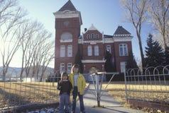 站立在一座农村法院大楼前面的兄弟和姐妹 库存图片