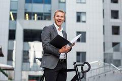 站立在一座办公楼的步的一个年轻商人,与纸和自行车文件夹  库存照片
