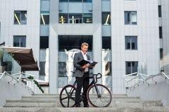 站立在一座办公楼的步的一个年轻商人,与纸和自行车文件夹  免版税库存照片
