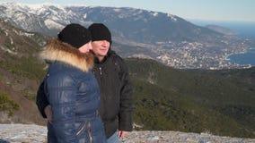站立在一座多雪的山顶部的妇女和人 影视素材
