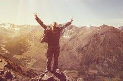 站立在一座山顶部用被举的手和享受日出的远足者 免版税库存图片