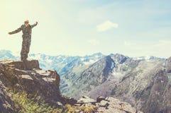 站立在一座山顶部用被举的手和享受日出的远足者 免版税图库摄影