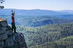 站立在一座山顶部的年轻人远足者用被举的手,庆祝成功 与拷贝的全长射击 图库摄影