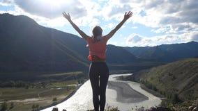 站立在一座山顶部的远足者妇女用手rised  后面看法、旅行和休闲 免版税库存图片